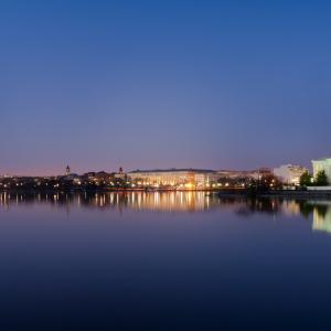 Washington DC at dusk. The Washington Memorial stands illuminated on the left. The Jefferson Memorial, also illuminated stands to the right. The river runs in the foreground.