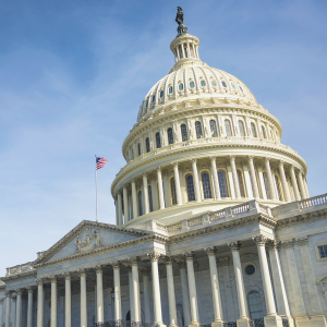 Image of the United States Capitol. The building fits in the bottom right side of the image, while a blue sky with light clouds rises up behind it.
