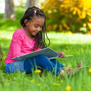 young girl reading book outside fall leaves on tree