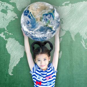 Girl holding the Earth over her head smiling