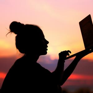 woman holding computer outside at sunset