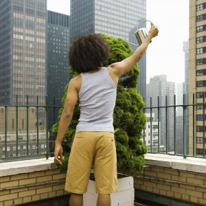 Man with curly hair watering a plant on a city rooftop (Image via Shutterstock)