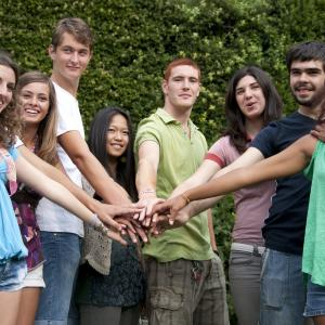 A group of young adults putting their hands together
