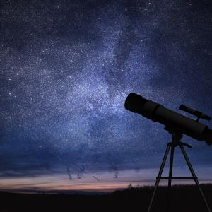 Telescope against a backdrop of a plethora of stars amidst midnight blue