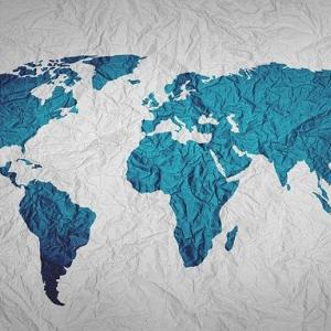 A world map with landforms in blue on wrinkled fabric