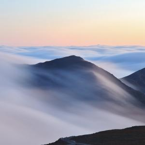 An inversion trapped low level moisture making for a stratus layerthat flowed over and around neighboring peaks.