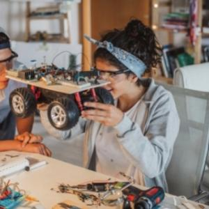 Two people building an electric vehicle model using recycled materials