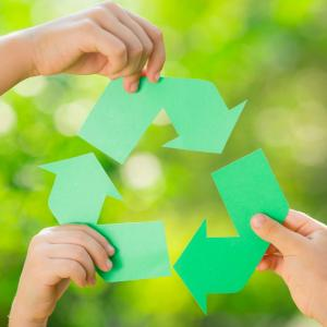 Three hands holding sections of the recycle symbol.