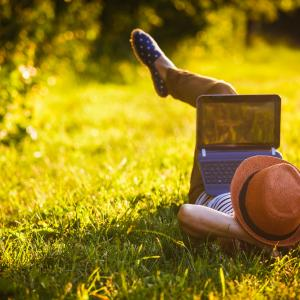 Person lying down on grass With laptop.