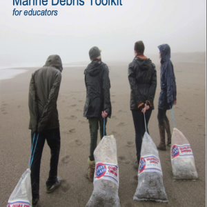 Four people dragging large bags of marine debris across a beach.