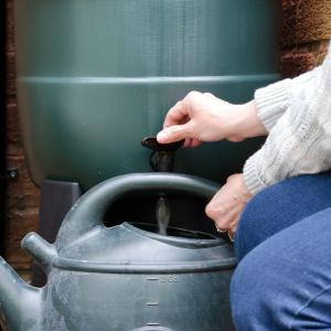 Woman getting rainwater from storage tank to use for gardening
