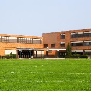 red brick school building and green grass