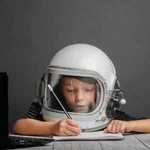 Child wearing an astronaut's helmet and holding a pencil.