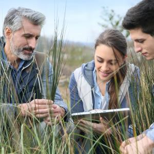 teacher with high school students looking at laptop in field