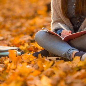 student sitting on autumn leaves writing in notepad