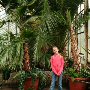 young student standing in greenhouse