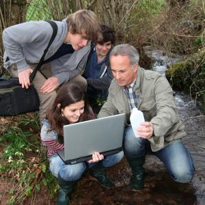 teacher and students looking at laptop at rivers edge