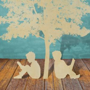 paper cutouts of two students reading under tree, sitting on brown wood floor in front of suggested painted blue bricks