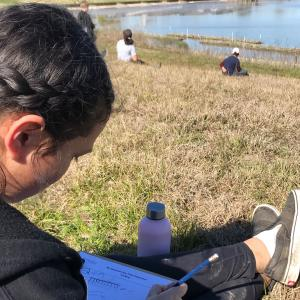 girl sits on grass by water writing in notebook