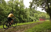 Person bicycling along an historical canal trail.